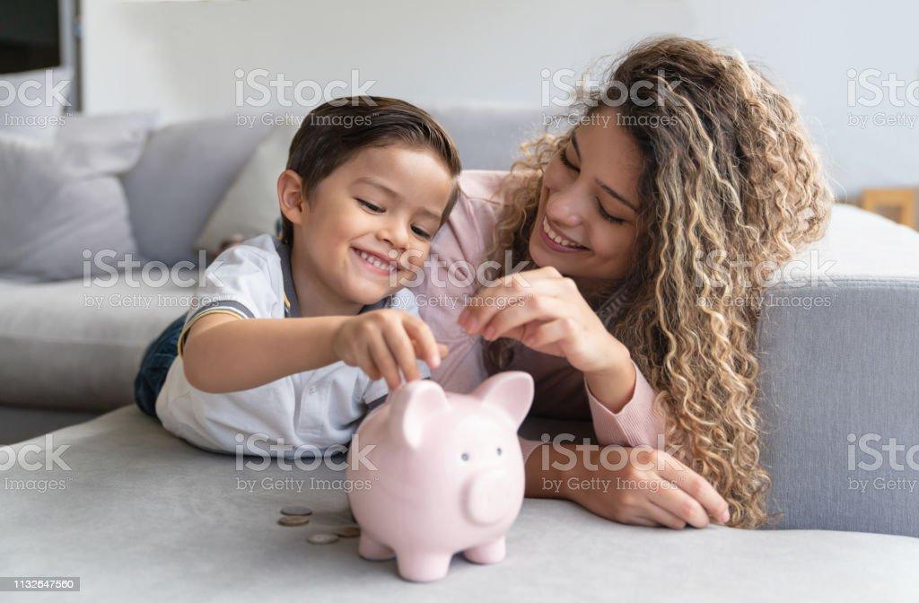Mutlu anne ve oğul tasarruf para içinde bir piggybank - Royalty-free Aile Stok görsel