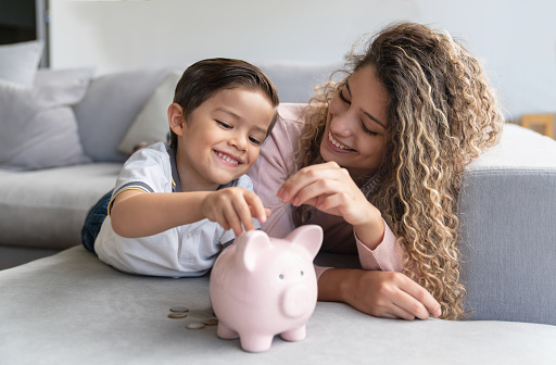 Portrait of a happy mother and son saving money in a piggybank and smiling - home finances concepts
