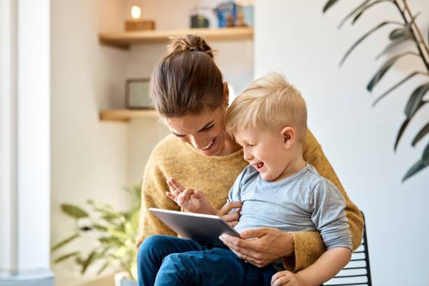 mutlu anne ve oğlu evde dijital tablet kullanma - i̇skandinav kültürü stok fotoğraflar ve resimler