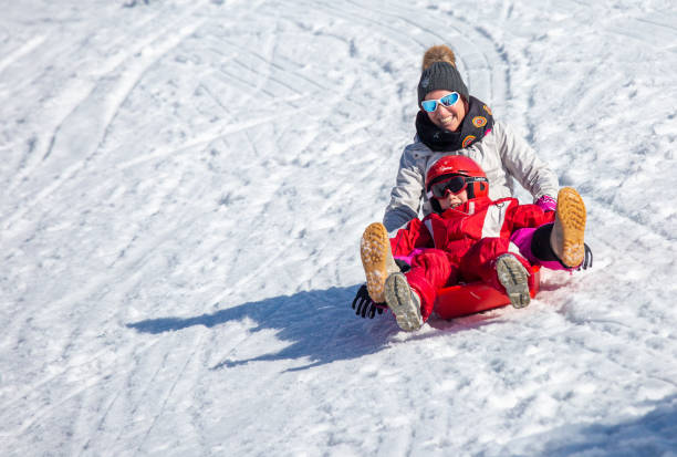 Happy mother and sot sliding on snowy slope stock photo