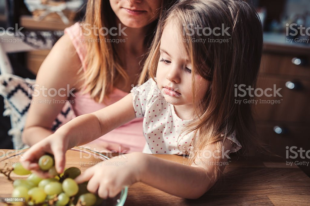 happy mother and toddler daughter having breakfast in kitchen stock photo