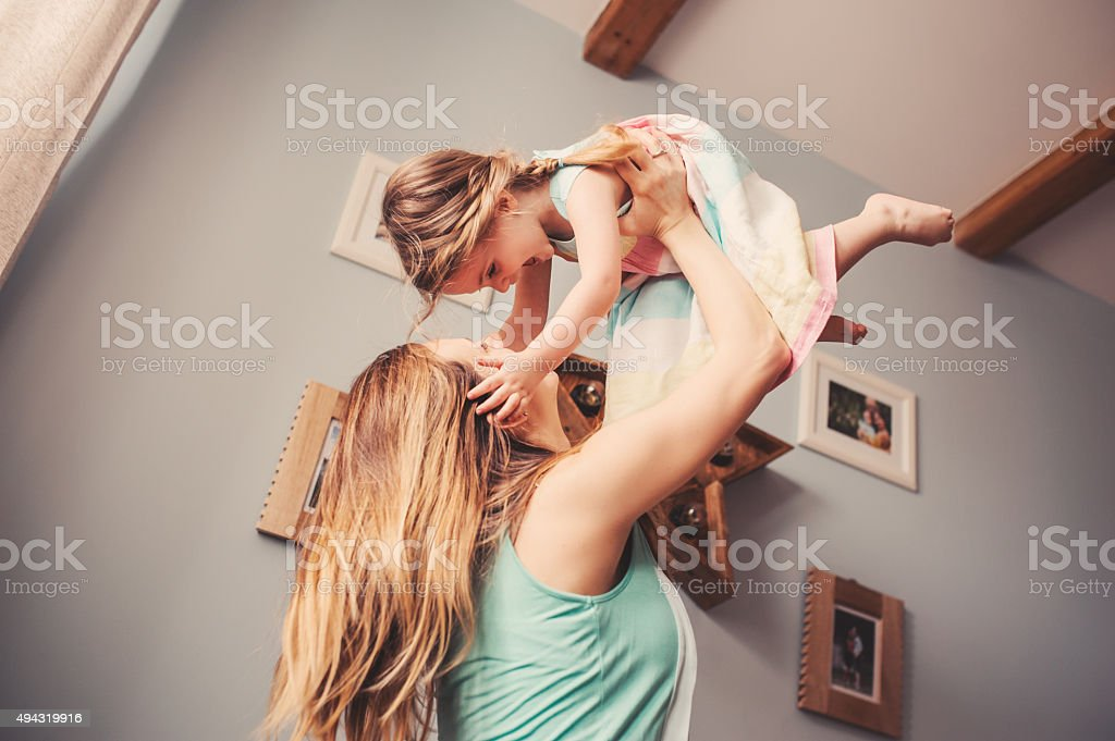 happy mother and toddler daughter playing together at home stock photo