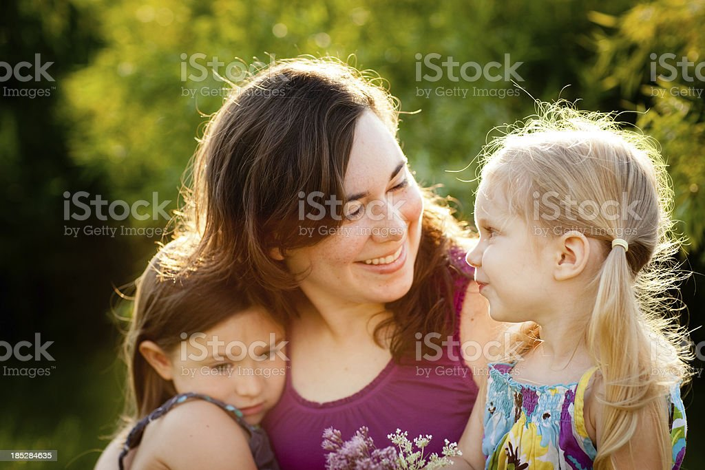 Happy Mother and Two Daughters Sitting Together Outside stock photo