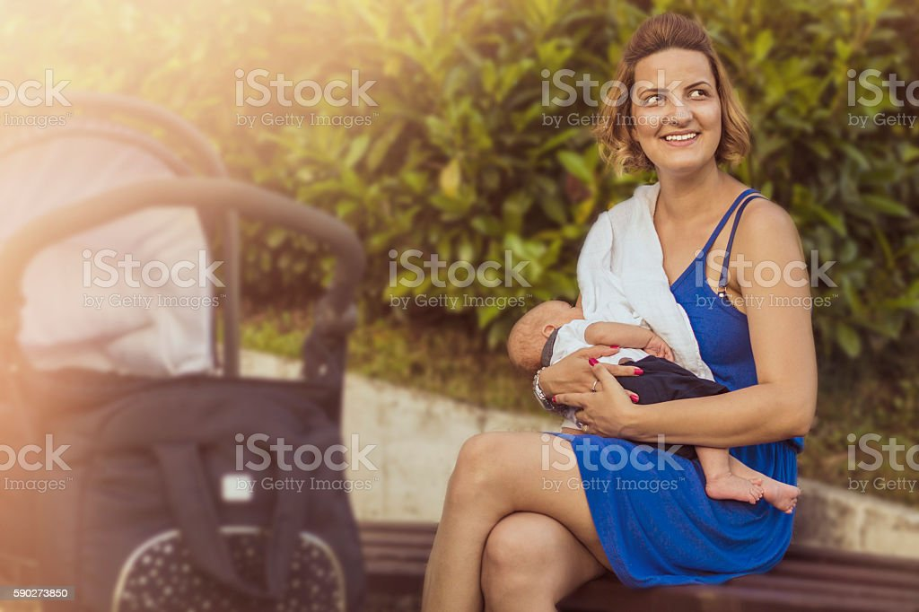 Happy mother breastfeeding her newborn baby in public on sunlight stock photo