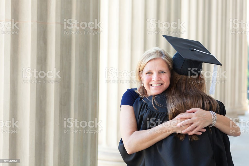 88982393c13 Happy Mother Congratulating Hugging Daughter in University Graduation  Ceremony royalty-free stock photo