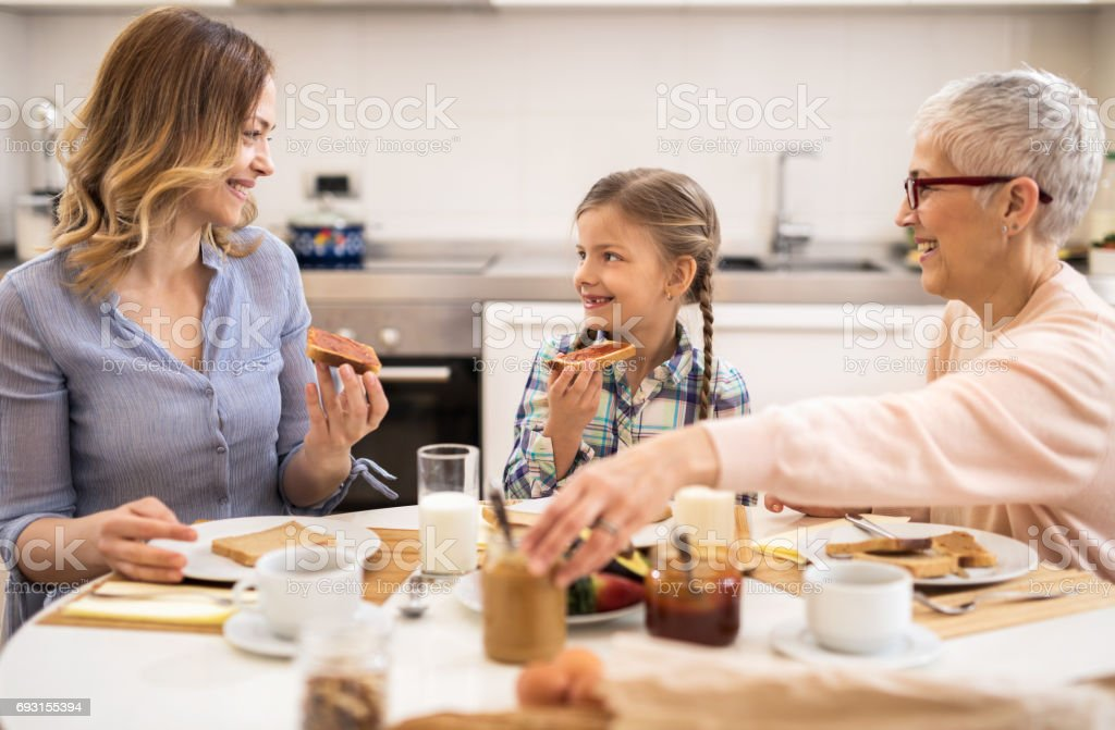 Happy mother, daughter and grandmother communicating during breakfast in the kitchen. stock photo