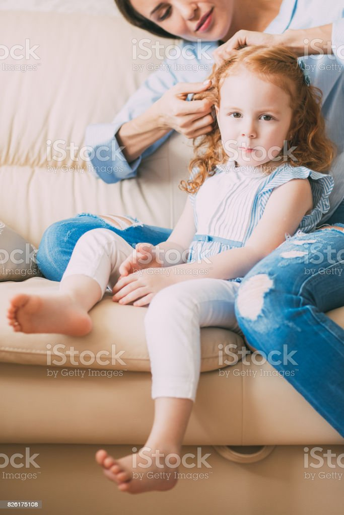 Happy mother doing hair of serious little daughter stock photo