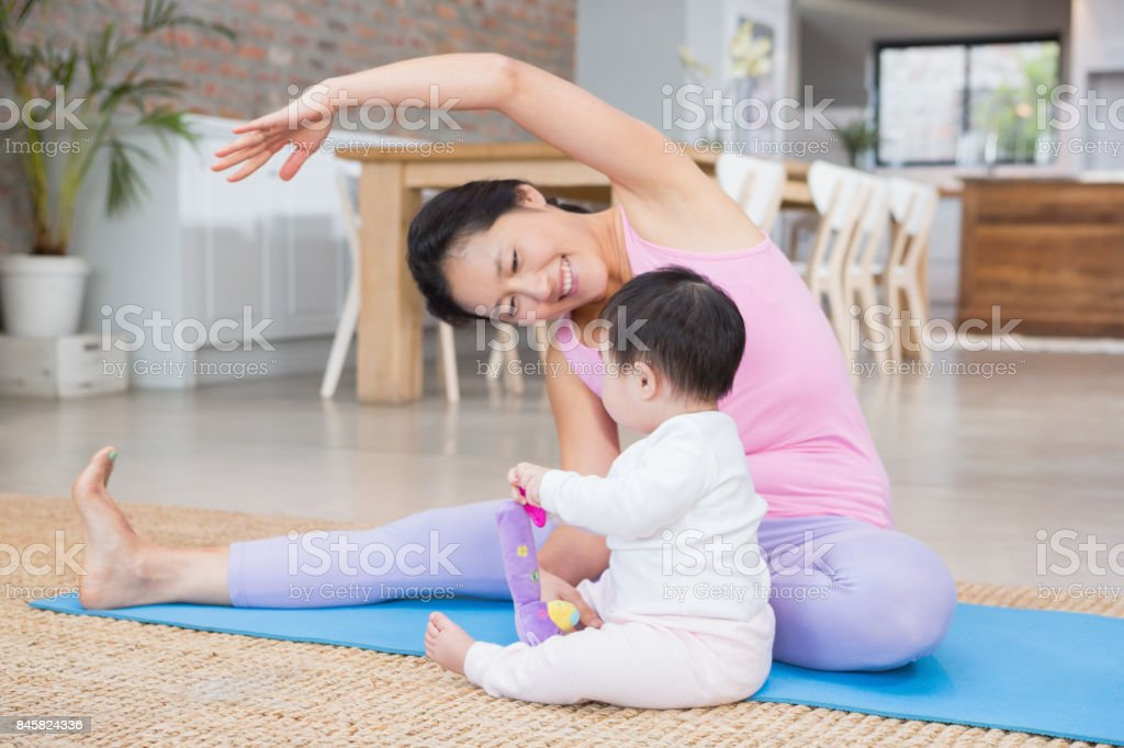 Happy mother doing yoga on mat while looking at baby daughter stock photo