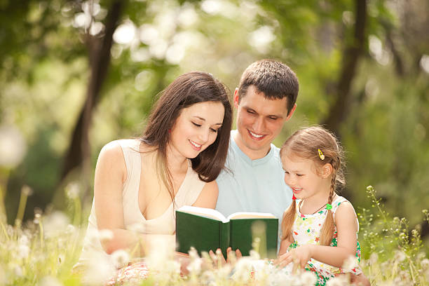 Glückliche Mutter, Vater und Tochter ein Buch zu lesen – Foto