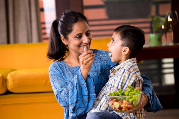Glückliche Mutter füttert Obstsalat an Sohn – Foto
