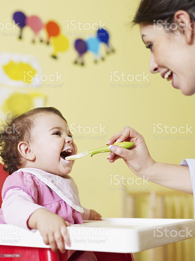 Happy mother feeding her cute baby stock photo