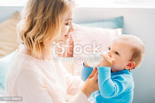 happy mother feeding her little child with baby bottle at home