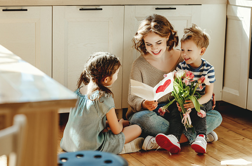 Smiling young woman reading greeting card while sitting on floor with cheerful little siblings with bouquet of flowers during mother day