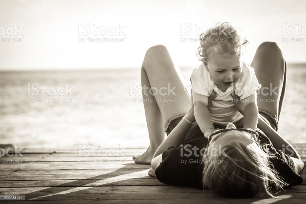 Happy mother having fun  with her child baby  lying on pier with sunlight during summer beach holidays in black and white stock photo