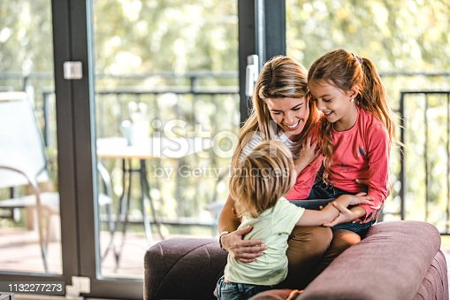 1159543952istockphoto Happy mother having fun with her son and daughter at home. 1132277273