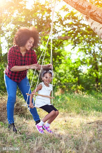 istock Happy mother having fun with your child on a swing 541292190