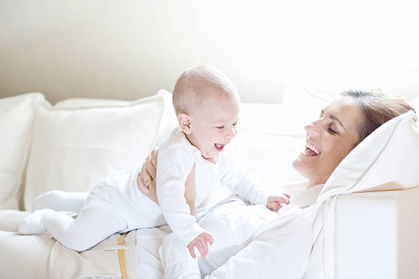 Happy mother holding her lovely smiling baby stock photo