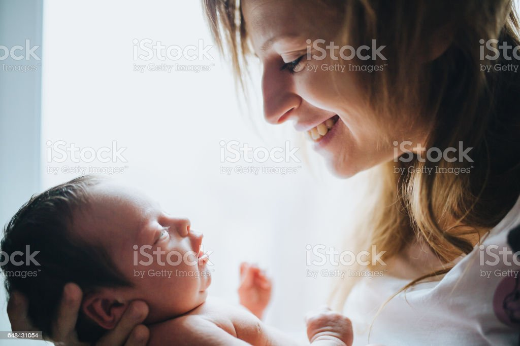 Happy mother holding her small newborn baby stock photo