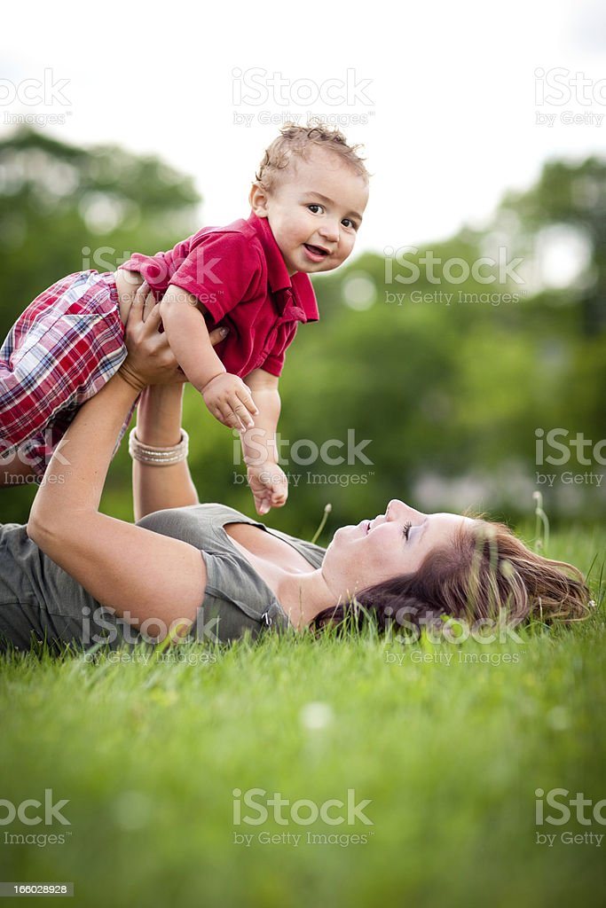 Happy Mother Holding Son While Lying in Grass Outside royalty-free stock photo