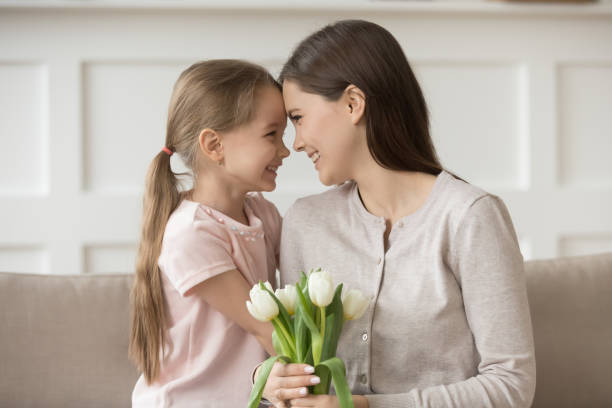 happy mother holding white tulips touches foreheads with daughter - little girls giving head stock photos and pictures