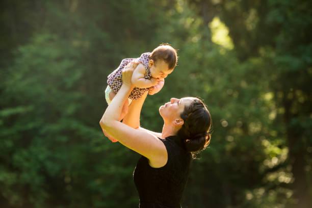 glückliche mutter hält ihre baby-tochter im freien - kemter stock-fotos und bilder