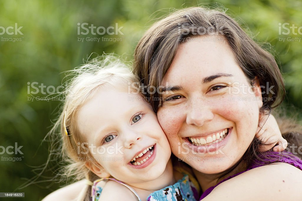 Happy Mother Hugging and Kissing Her Daughter Outside stock photo