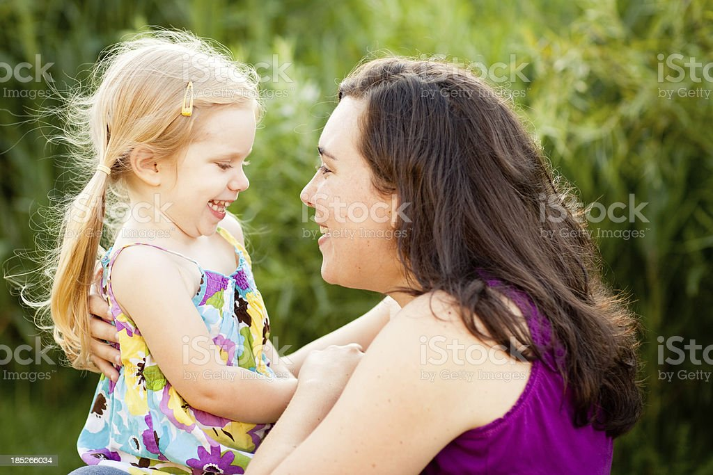 Happy Mother Hugging Her Daughter Outside On Summer Day stock photo