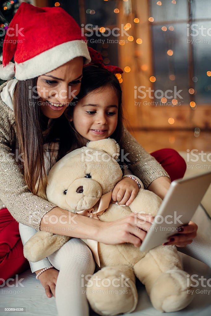 Happy mother in santa claus hat  with her daughter stock photo