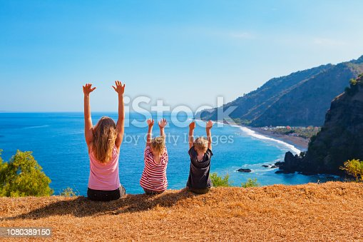 929671306 istock photo Happy mother, kids on hill with sea cliffs scenic view 1080389150