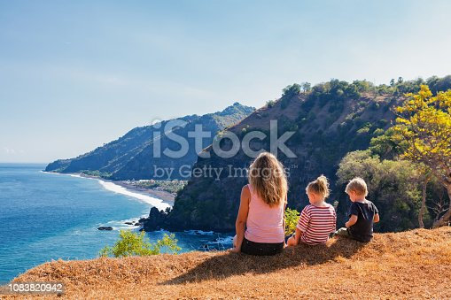 929671306 istock photo Happy mother, kids on hill with sea cliffs scenic view 1083820942