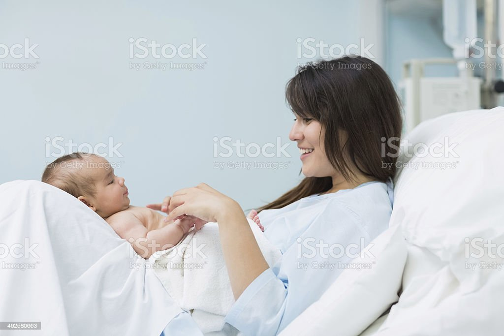 Happy mother lying with a new born baby on her stock photo