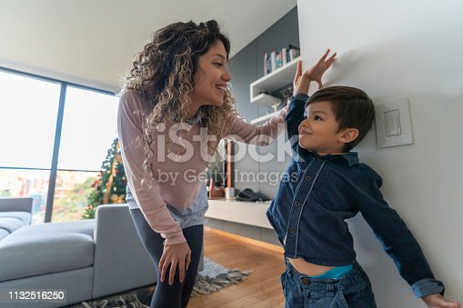 Happy mother measuring her son at home against the wall – parenting concepts