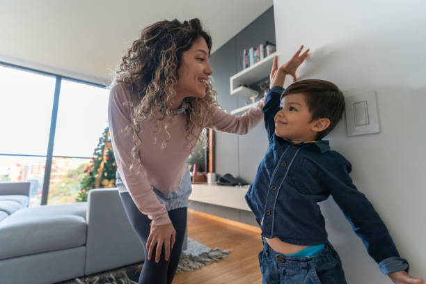 happy mother measuring her son at home - height measurement stock photos and pictures