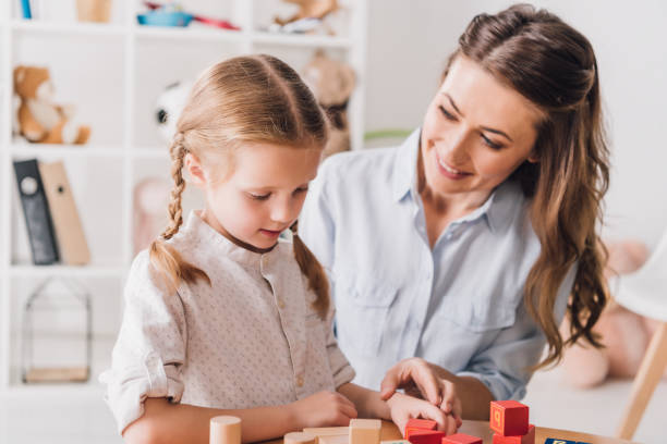 happy mother playing blocks with little child happy mother playing blocks with little child autism stock pictures, royalty-free photos & images
