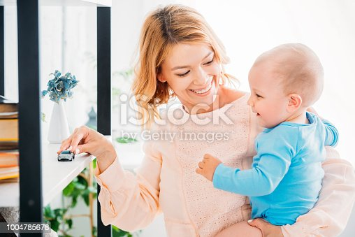 istock happy mother playing with child and riding toy car on bookshelf 1004785678