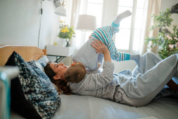 Happy mother playing with her toddler lying in bed stock photo