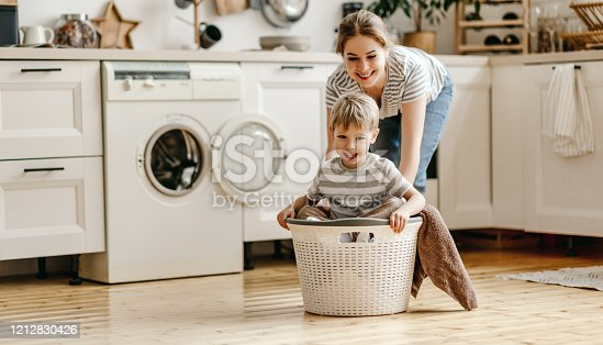Cheerful young woman laughing and pushing basket with son while having fun in cozy kitchen in weekend