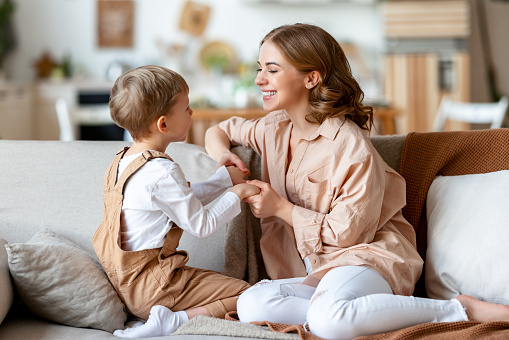 Happy mother playing with son on sofa
