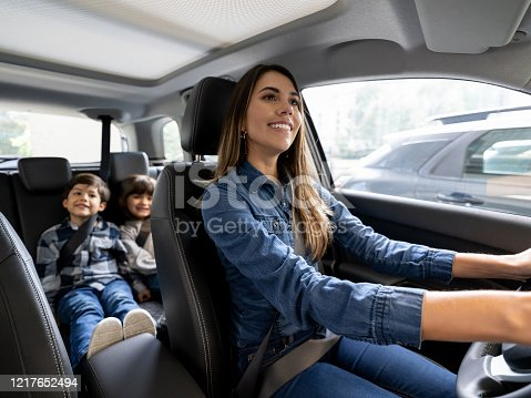 Happy Latin American mother riding in the car with her kids and smiling while wearing their seatbelts