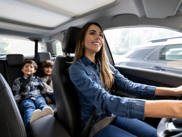 Happy mother riding with her kids in the car stock photo
