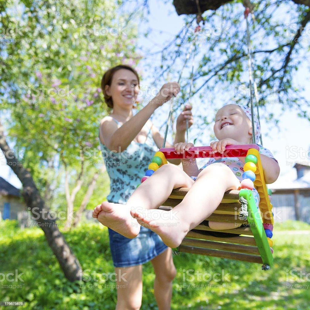 Feliz madre con bebé sonriente balancín on swing foto de stock libre de derechos