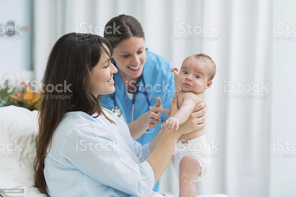 Happy mother smiling while holding a baby boy in diaper royalty-free stock photo