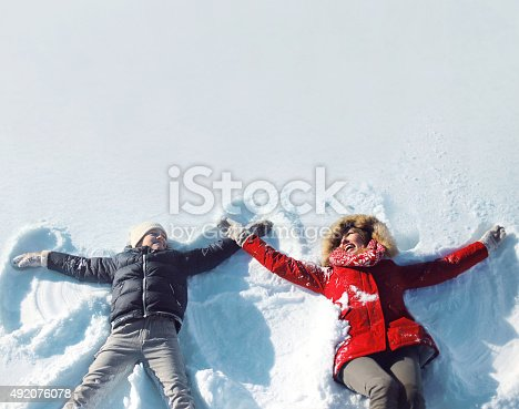 istock Happy mother, son playing having fun lying in snow winter 492076078