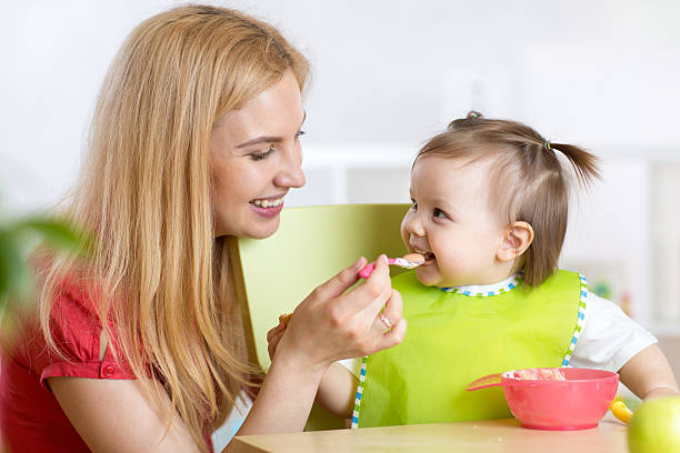 Happy mother spoon feeding her baby child stock photo