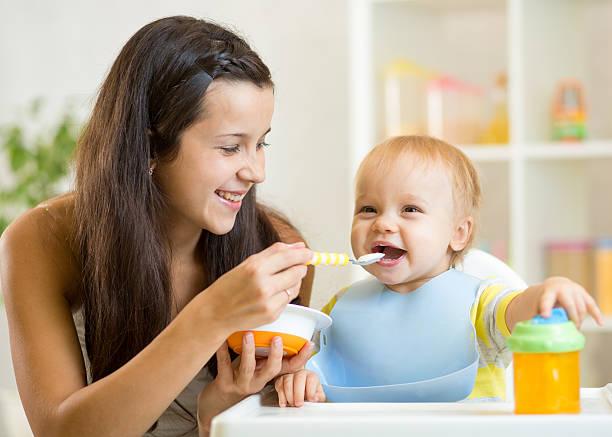 Glückliche Mutter Löffel füttern Ihr baby Kind – Foto