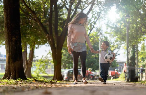 happy mother taking her son to school - aree esterne della scuola foto e immagini stock