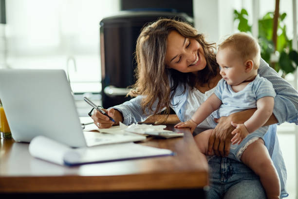 happy mother talking to her baby while working at home. - orçamento imagens e fotografias de stock