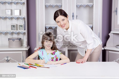istock Happy mother teach her daughter to paint. 594482054