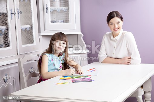 istock Happy mother teach her daughter to paint. 594482200