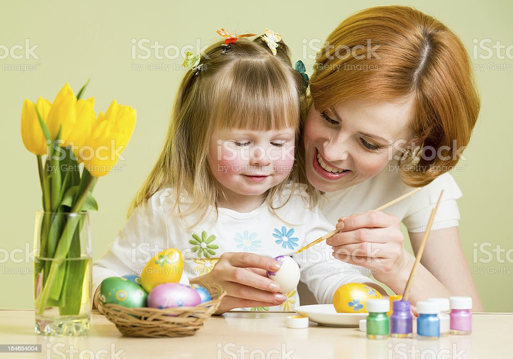 happy mother teaches daughter to paint easter eggs royalty-free stock photo